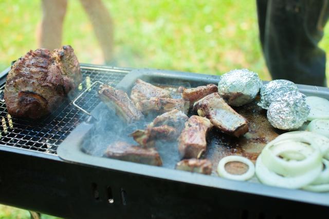 鉄板の乗ったバーベキュー網と肉